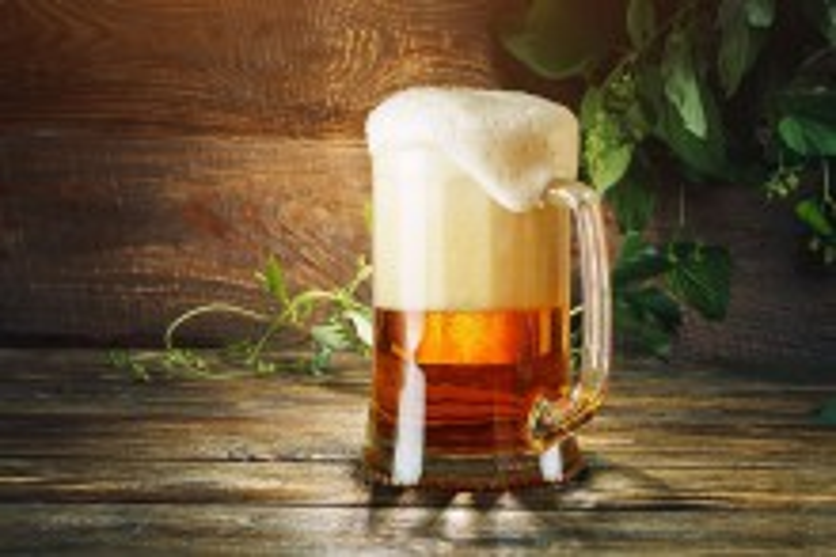 Ein Glas frisches Biers und grünes Hopfen auf einem Holztisch.