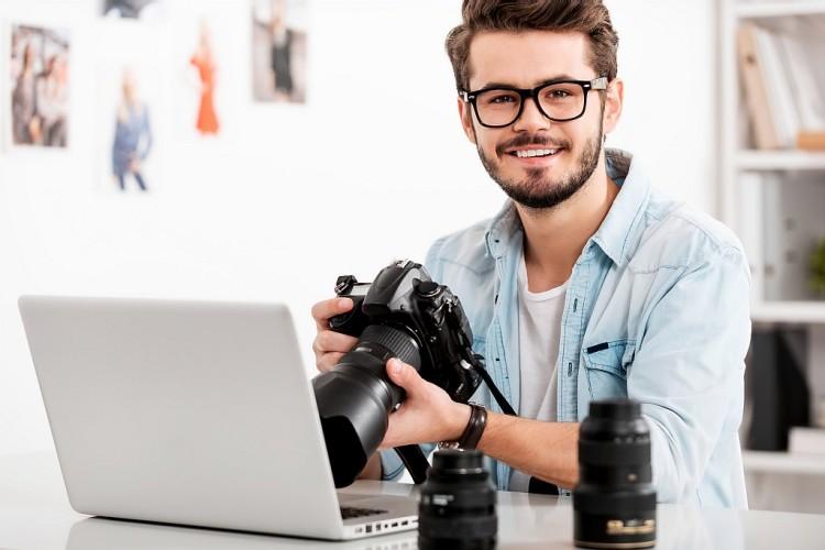 Glücklicher junger Fotograf, sitzt vor einem Laptop und hält eine Kamera
