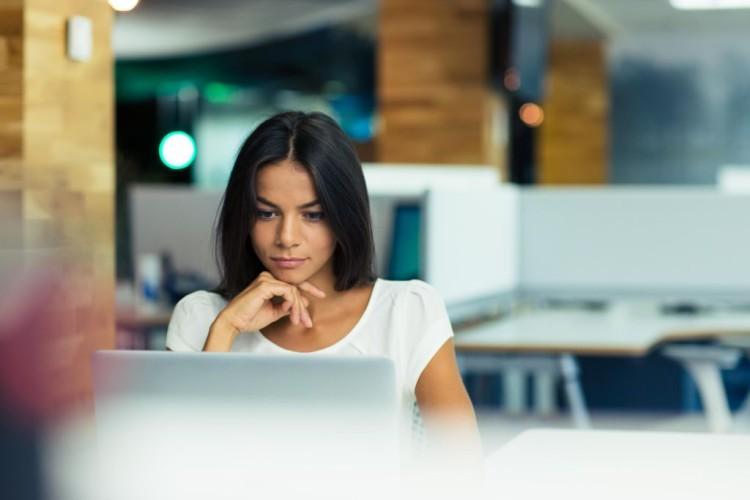 Eine junge Frau sitzt vor einem Notebook